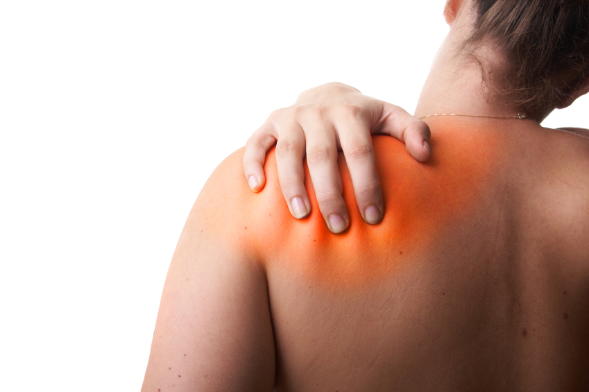 Mulher de costas com as mãos no ombro como se sentisse dor