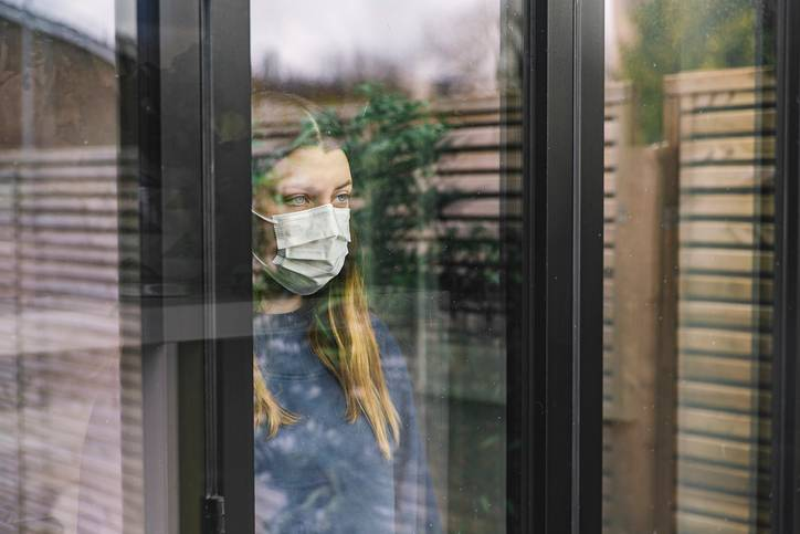 Mulher com mascara atrás de uma janela