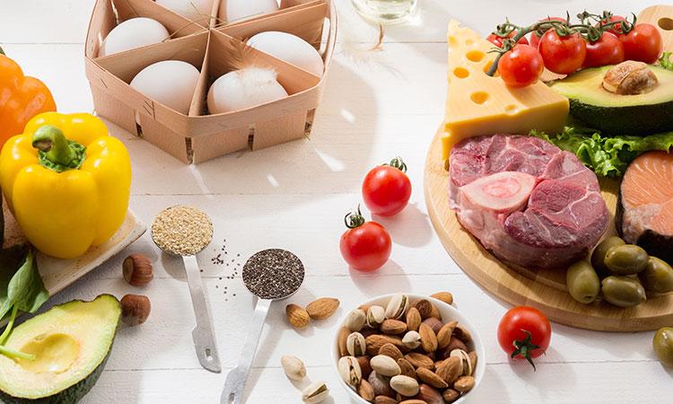 Ovos, pimentão queijo, carnes e sementes postos sobre uma mesa.