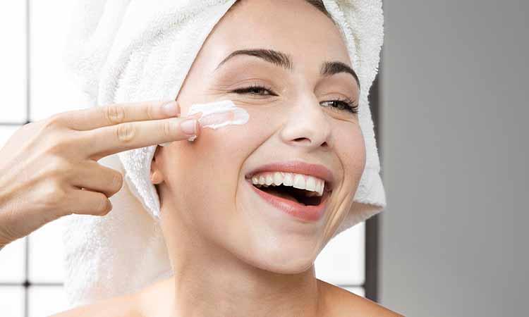Mulher de toalha branca na cabeça sorrindo e uma mão em seu rosto aplicando um creme