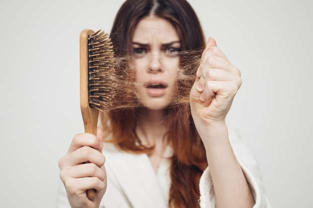 mulher segurando uma escova de cabelo, puxando os cabelos da escova na outra mão