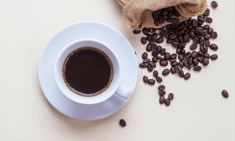 xicara e pires de um café em cima da mesa com o café liquido dentro e sobe a mesa se encontram grãos de café espalhados