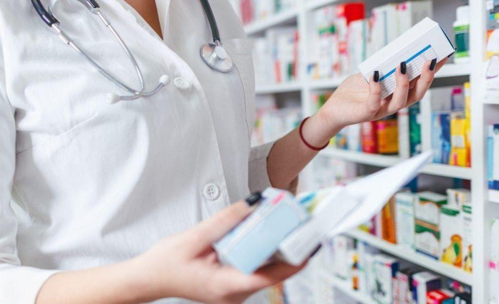 mulher com jaleco branco segurando caixas de remédio na mão