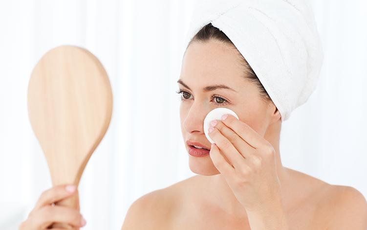mulher com toalha na cabeça segurando um espelho e com a outra mão segurando um algodão perto dos olhos