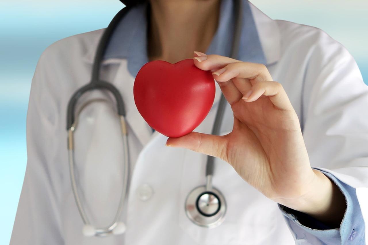 mulher com jaleco branco segurando um coração vermelho