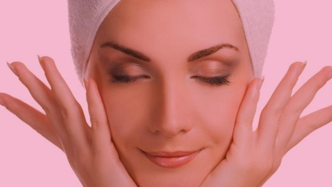 Rosto de uma mulher com os olhos fechados e com as mãos abertas no rosto