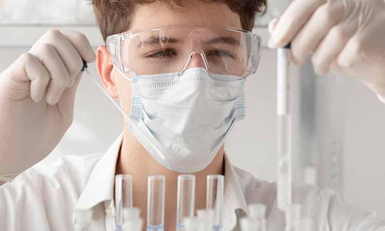 Homem segurando um conta gota e vários tubos transparentes