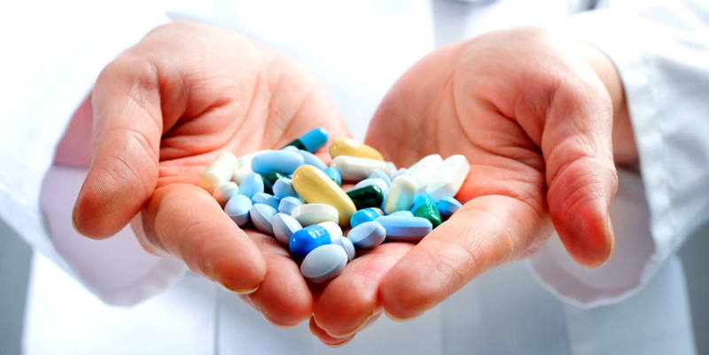duas mãos com várias capsulas azul e amarela