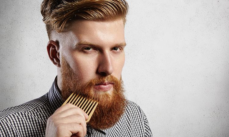 Homem ruivo pentiando a barba