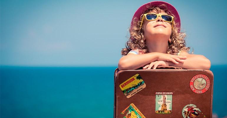 uma criança com oculos de sol e chapeu com uma mala na sua frente