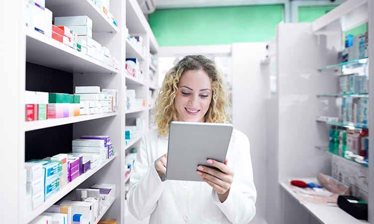 mulher loira sorrindo com um tablet na mão