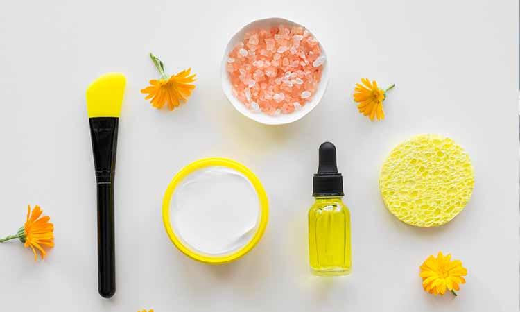 Pincel preto e amarelo, pote de creme, esponja, vidro com liquido amarelo e pote com pedrinhas rosas e brancas e flores amarelas