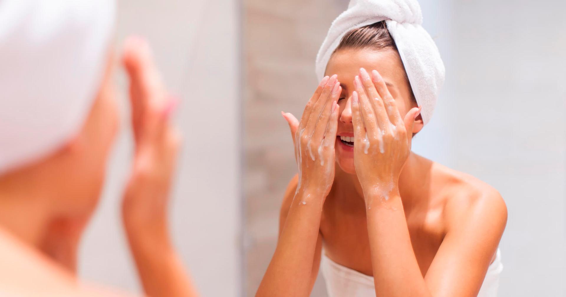 mulher de toalha com as mãos no rosto