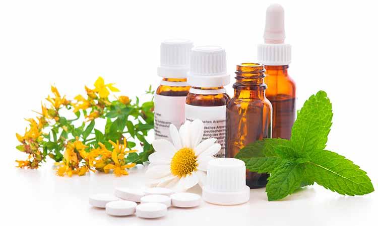 frascos de medicamento com capsulas branca em cima da mesa e flores branca e amarelas