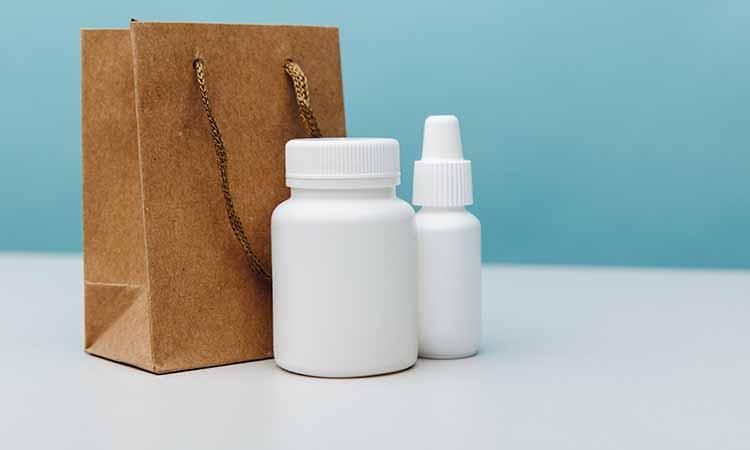 sacola marrom com dois potes brancos em cima de uma mesa