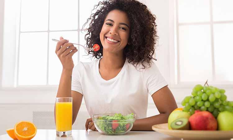 Mulher com cabelos escuros, segurando uma colher com um tomate entre eles, frutas em cima da mesa como laranja, maça, kiwi, uva e salada com tomates