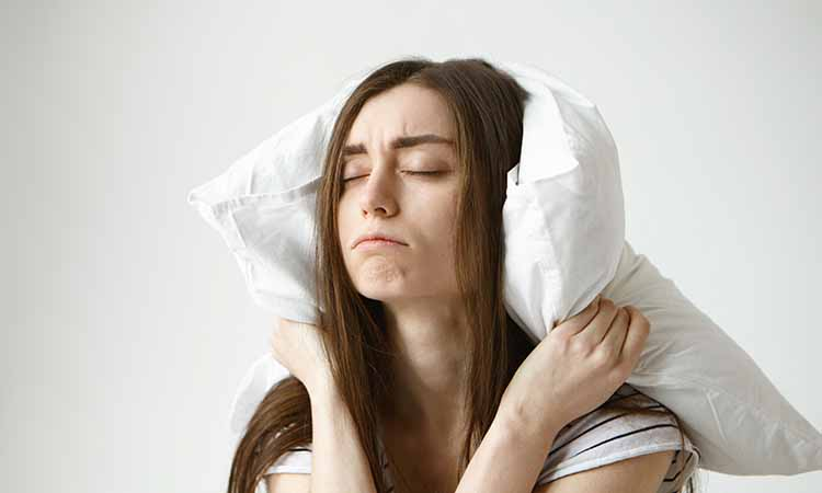 Mulher segurando um travesseiro atrás da cabeça de olhos fechados e feição de cansada