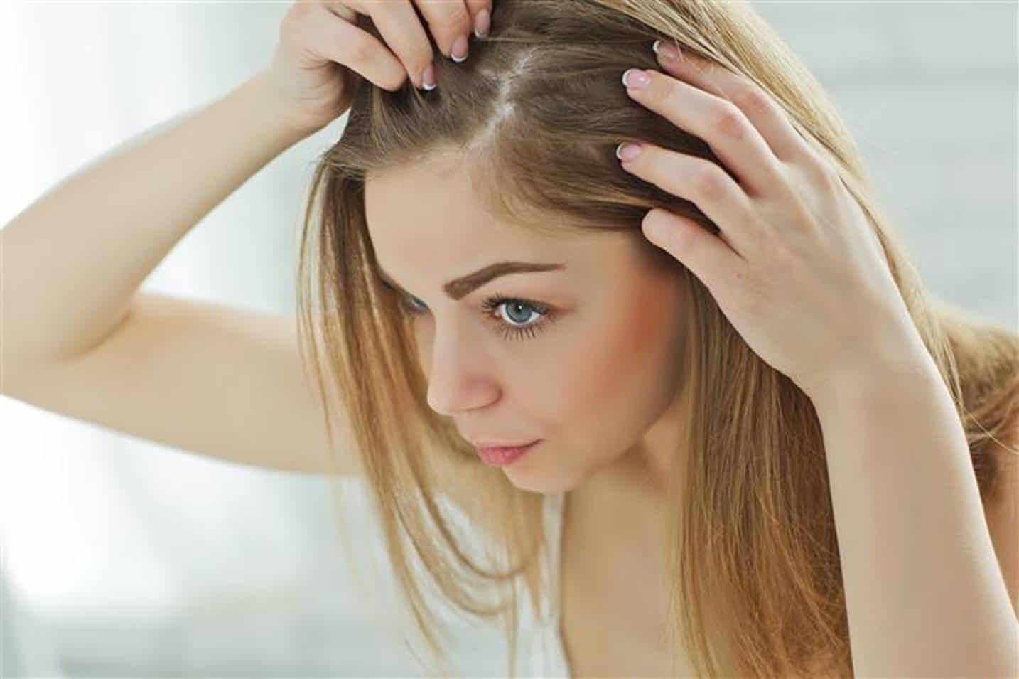 mulher com cabelos loiros com as mãos na raiz do cabelo