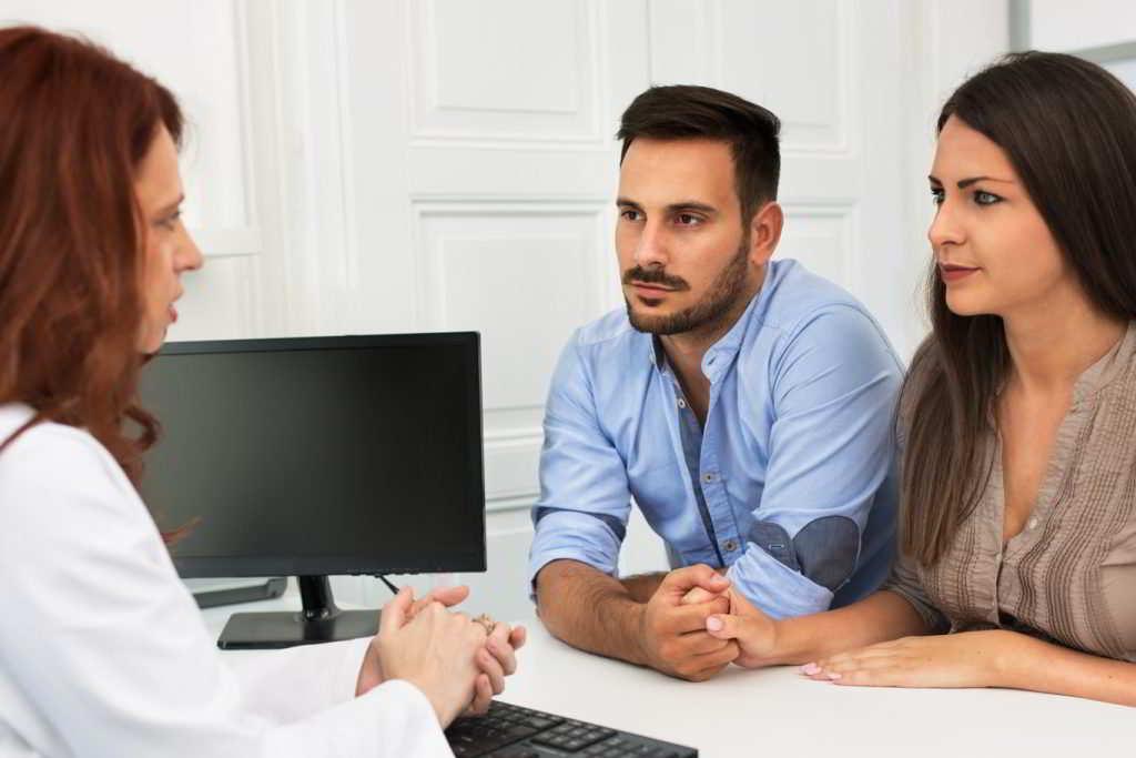 Três pessoas na foto, uma médica de cabelo ruivo e um casal que se encontram de mãos dadas e com um rosto serio