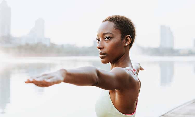 Mulher negra com camiseta branca com os braços levantados e retos