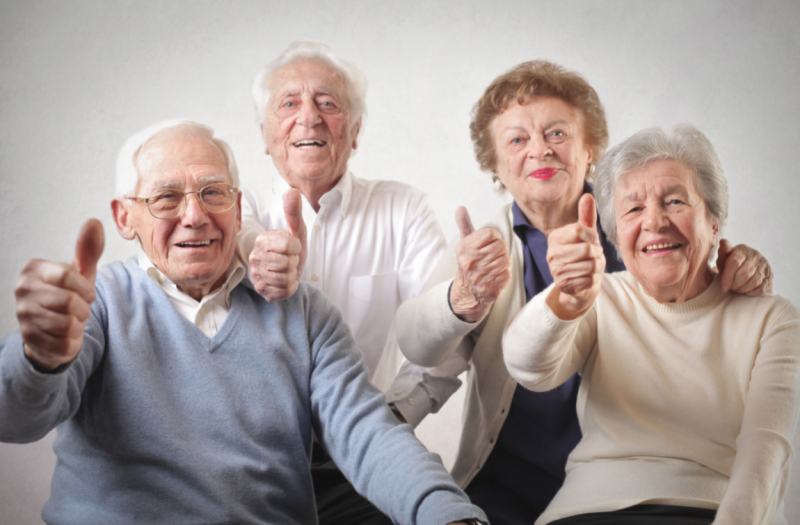 Dois homens e duas mulheres de idade fazendo joia com os dedos