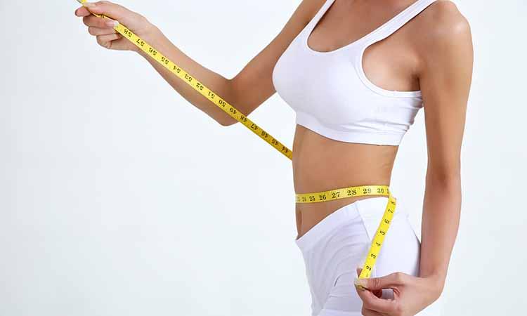 Corpo feminino envolvido por uma fita métrica de medidas