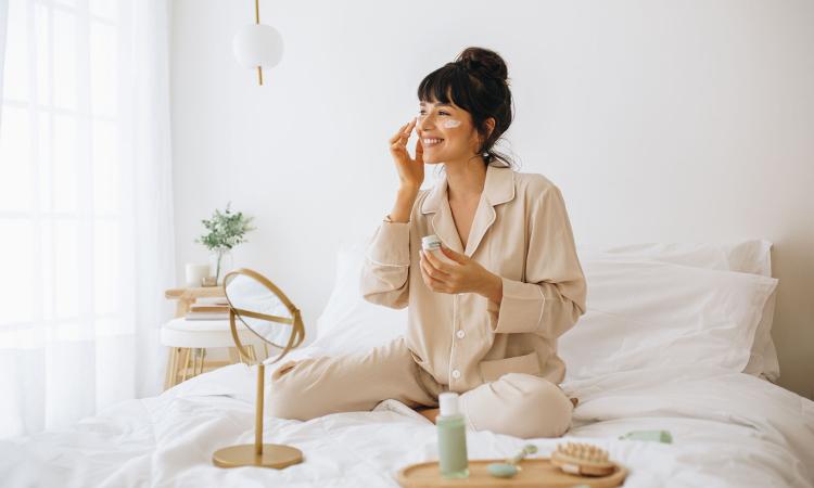 Mulher sentada na cama passando creme no rosto com alguns produtos em cima da cama e um espelho