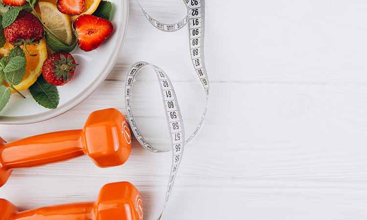 Imagem com uma fita de tirar medidas, dois alteres laranjas e um prato com frutas como morango, laranja e folhas verdes