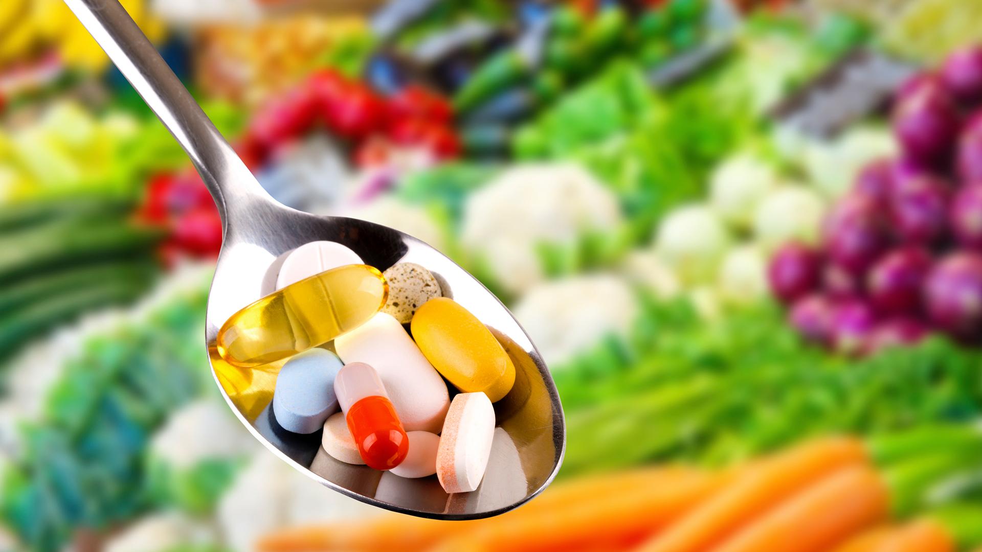 colher com diversas capsulas coloridas e legumes atrás da imagem