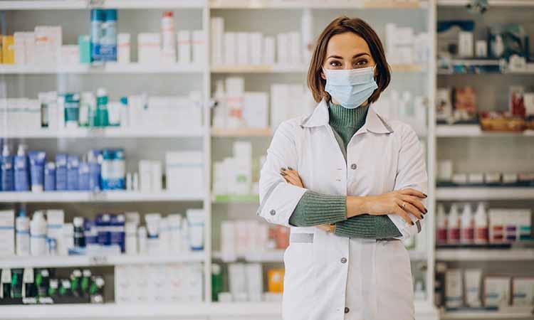 Imagem de uma farmacêutica com jaleco branco de mascara com diversos produtos na pratileira