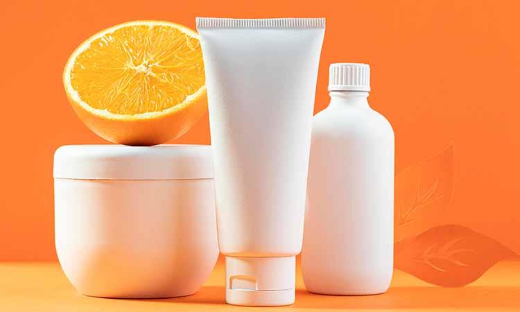 um pote branco e dois tubos brancos com metade de uma laranja em cima do pote branco