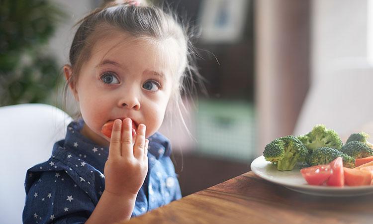 Criança comendo alimentos nutritivos